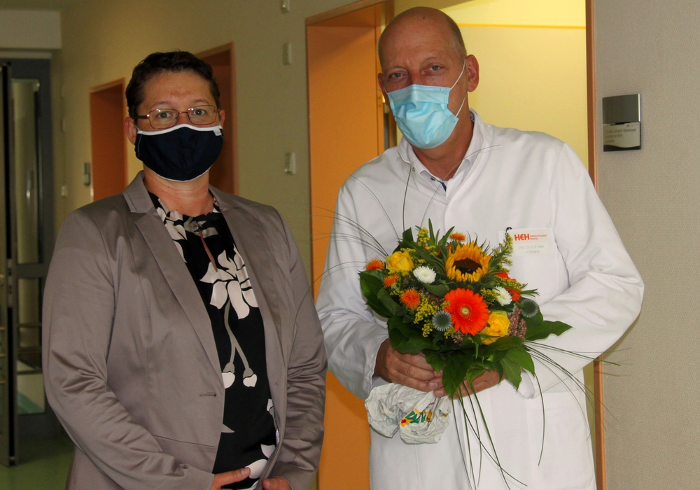 Geschäftsführerin Monika Skiba gratuliert Prof. Dr. med. Karl-Dieter Heller zum 20-jährigen Dienstjubiläum.