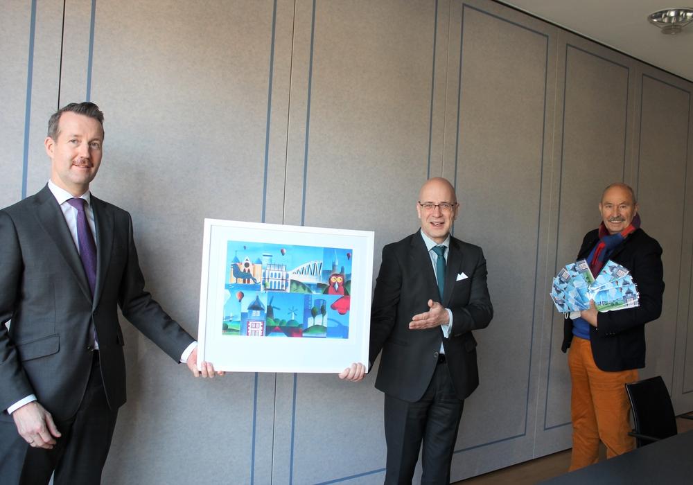 Michael Pannwitz, Leiter Individualkunden von der Volksbank BraWo (l.), präsentiert zusammen mit dem kommissarischen Leiter der Volksbank BraWo Direktion Salzgitter, Stefan Honrath (m.), und Hans-Joachim Grove (r.),  Vorstandsmitglied der Grove-Moldovan Art-Foundation und Inhaber der ROM-ART Galerie, die Kunstkarten, deren Erlös Salzgitteraner Kindern zugute kommt.