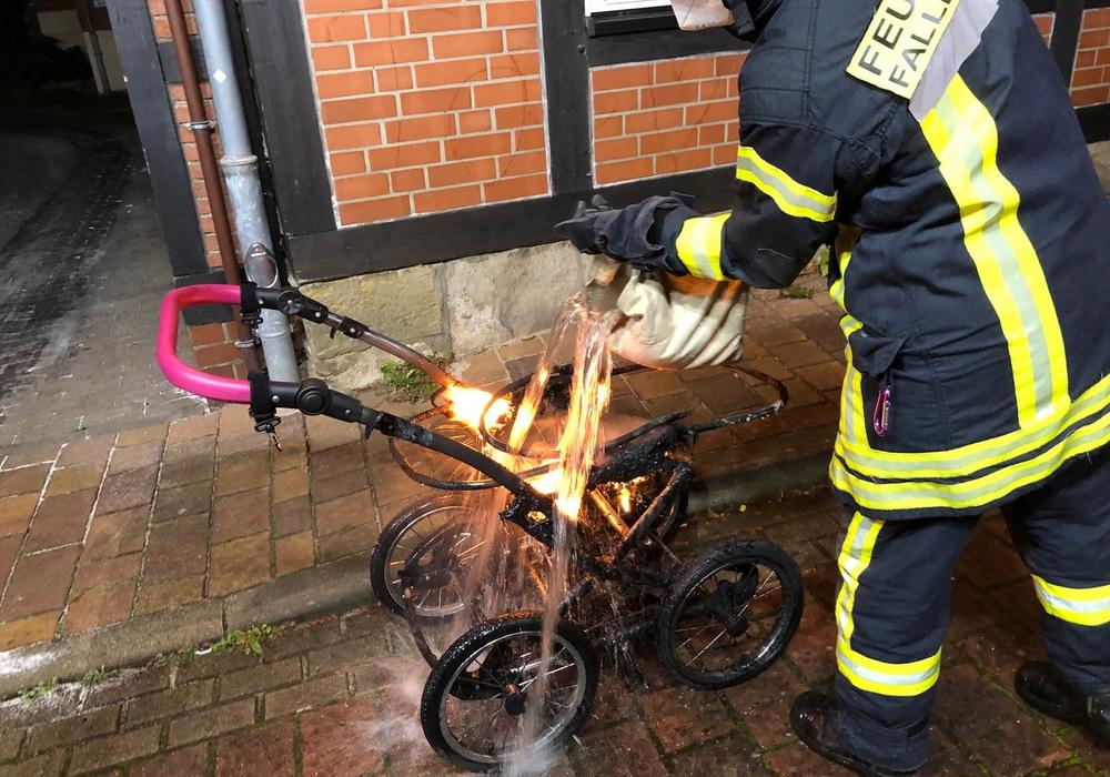 Ein Feuerwehrmann löscht den noch brennenden Kinderwagen.