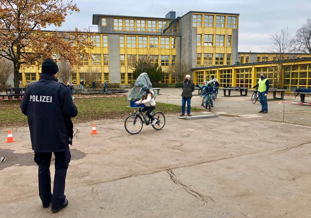 Alle dürfen ihr Geschick auf dem Fahrrad beweisen. Der Polizeibeamte schaut zu.