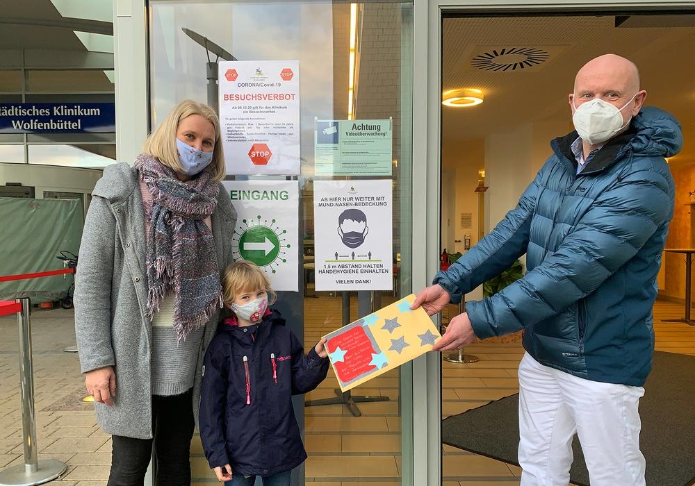 Stephanie Gäbel, Leiterin Kita Alter Weg, und Nike (5 Jahre) übergaben die Bilder an Dr. Tobias Jüttner, Chefarzt der Klinik für Anästhesie, operative Intensiv-, Notfall- und Schmerzmedizin.