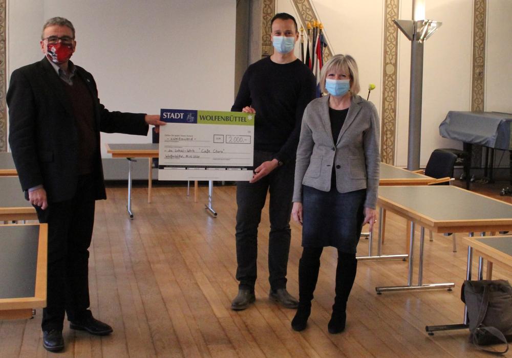 Bürgermeister Thomas Pink übergibt den Scheck an Norman Bialas und Petra Sarstedt-Hülsmann.