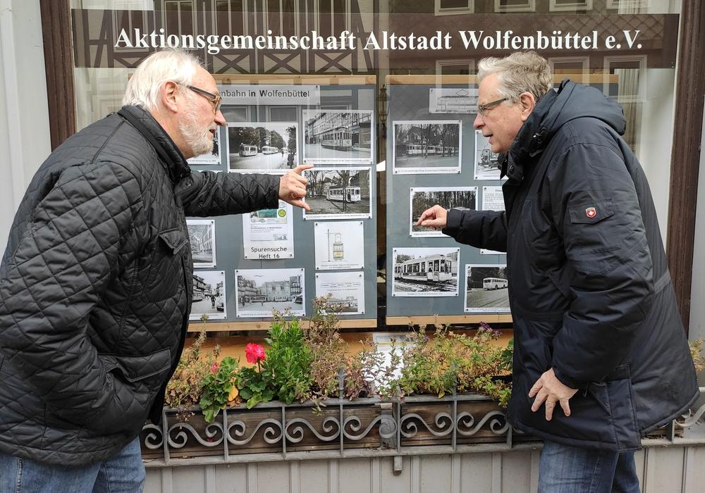 Heftautor Jürgen Hunger und Vereinsvorsitzender Dieter Kertscher vor dem Schaufenster der Aktionsgemeinschaft Altstadt Wolfenbüttel im Kleinen Zimmerhof. Hier bekommen Interessierte Informationen zur ehemaligen Straßenbahn in Wolfenbüttel präsentiert.