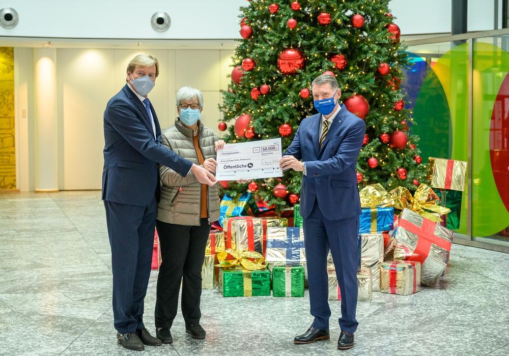Knud Maywald (rechts) übergibt die Spende der Öffentlichen für den Braunschweiger Fonds für Kinder und Jugendliche an Rüdiger Warnke und Friederike Harlfinger.