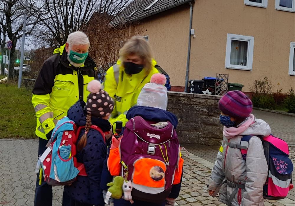 Klaus Seiffert von der Verkehrswacht und Silke Hitschfeld von der PI Wolfsburg-Helmstedt bei der Übergabe von Reflektionsmaterial an die Grundschulkinder.