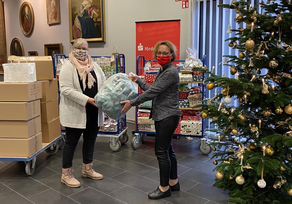 Anja Wiegand (re.) aus dem Orga-Team des Weihnachtswünschebaums übergibt die Spenden an Heike Malek vom Parkbank e.V..