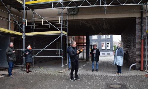 Projektleiter Artur Dorn beginnt im Innenhof seine Baustellenführung (Mitte).