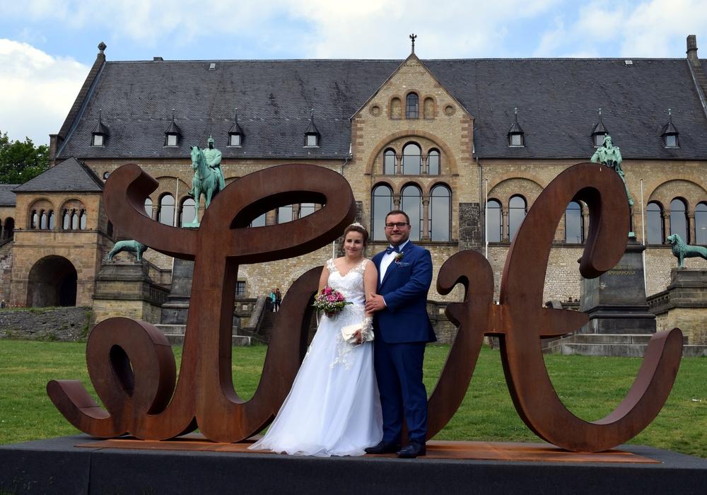 Ein Brautpaar posiert an der LoveHate-Skulptur vor der Kaiserpfalz.