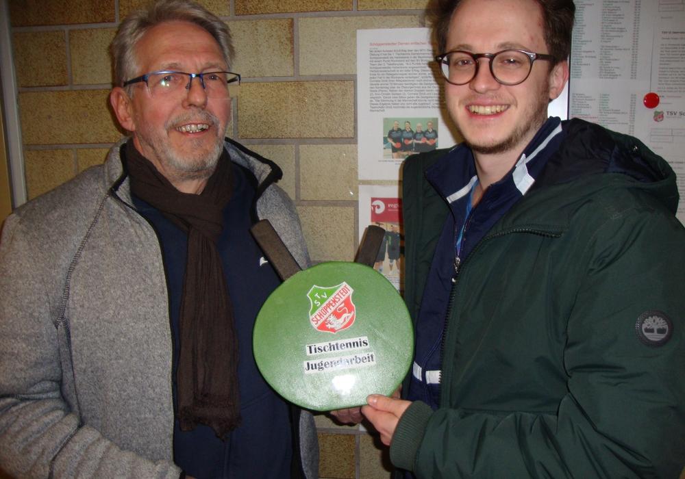 Detlef Singelmann (links) übergibt Sportwart Janek Lühr eine selbst gefertigte Spendendose in Form von Tischtennisschlägern.