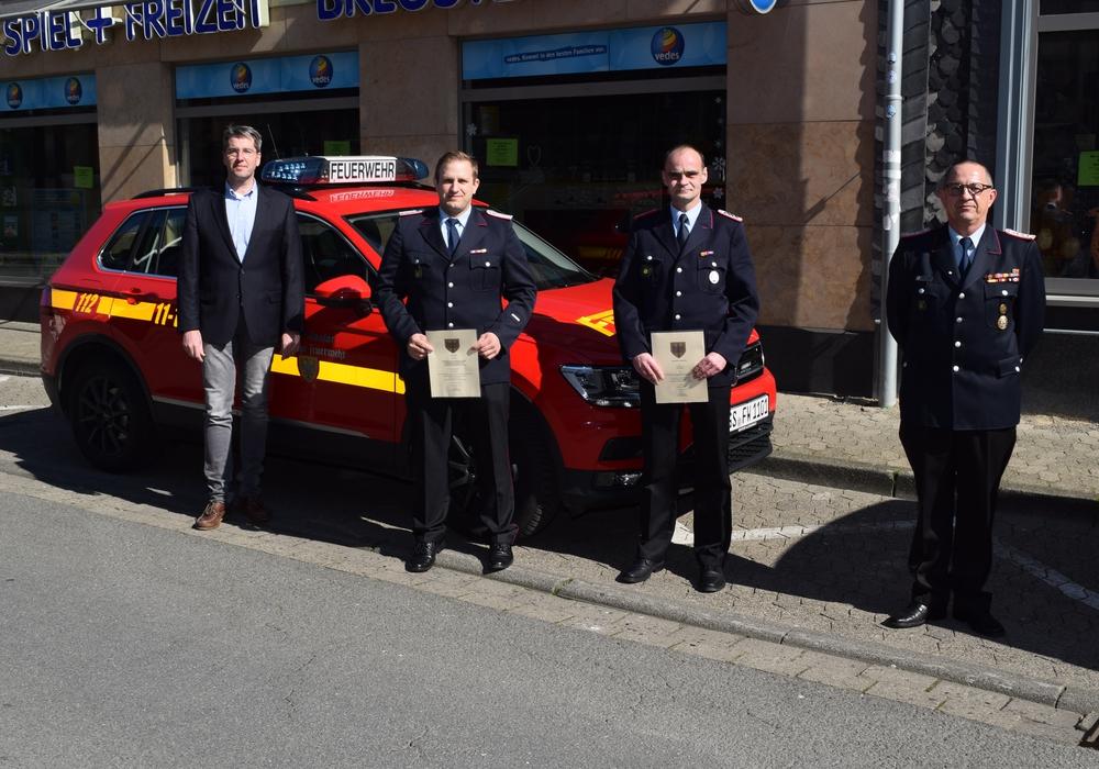 (von links) Oberbürgermeister Dr. Oliver Junk, Sebastian Rau, Kai Schmidt und Stadtbrandmeister Christian Hellmeier stehen gemeinsam vor einem Einsatzwagen der Feuerwehr.