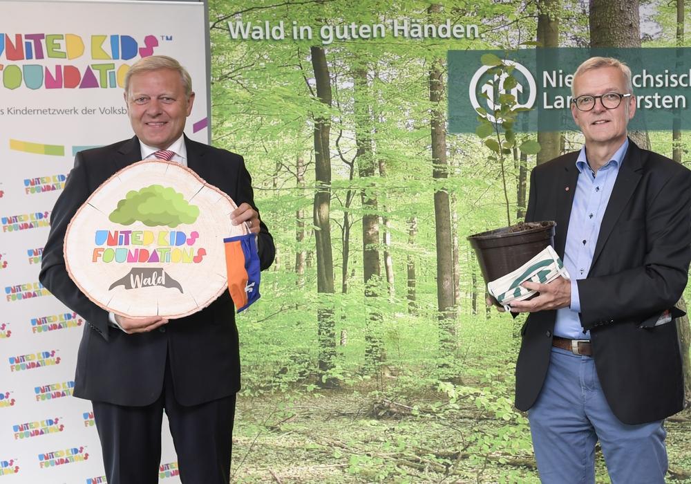 Jürgen Brinkmann, Vorstandsvorsitzender der Volksbank BraWo und Initiator von United Kids Foundations, und Dr. Klaus Merker, Präsident der Niedersächsischen Landesforsten, gründen den United Kids Foundations Wald im Harz nahe Torfhaus. Die Volksbank BraWo spendet dem Kindernetzwerk 15.000 Bäume zur Aufforstung.