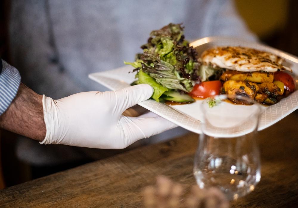 Servieren in Corona-Zeiten: Ohne Hygiene- und Abstandsregeln geht nichts in der Gastronomie. Daher sollten Gäste beim Restaurantbesuch Geduld mitbringen, meint die Gewerkschaft NGG.