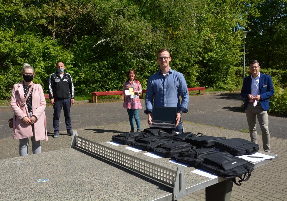 Bei der Übergabe der neun Laptops trafen sich auf dem Schulhof an der Tischtennisplatte Eltern mit Schulleiterin Sabine Nolte (hinten Mitte) und (rechts daneben) Fabian Adam und Björn Försterling vom Roten Kreuz.