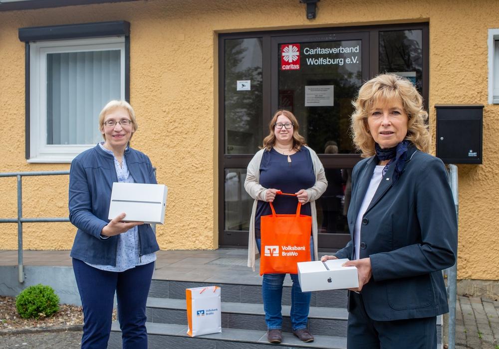 Claudia Kayser, Leiterin der Direktion von der Volksbank BraWo (rechts) überreicht vier iPads für die Seniorenarbeit an Barbara-Maria Cromberg (Vorständin) und Annika Scharenberg (Koordinatorin der Seniorenarbeit) vom Wolfsburger Caritasverband.