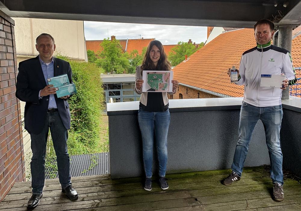 """Bürgermeister Klaus Saemann nahm als Vorsitzender der Bürgerinitiative """"Wir sind für Euch da"""" die Spende der Kaufmannsgilde von Ole Siegel (rechts) entgegen. Noreen Klöpper von PeineMarketing war mit dem Bild der Siegermaske von Conny Röhrich ebenfalls vor Ort."""