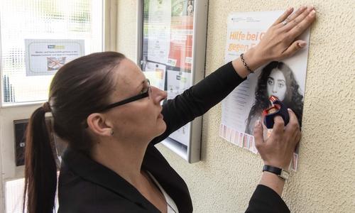 Yvonne Beyer von der TAG Wohnen klebt das erste Plakat in eine der Wohneinheiten der TAG.