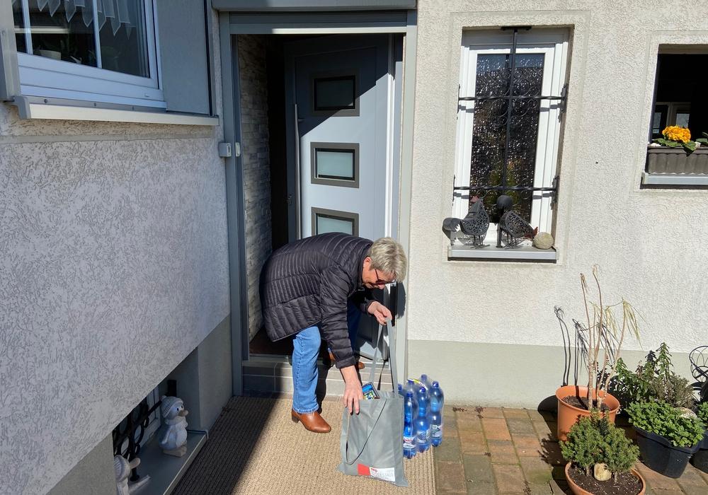 Eine Frau freut sich über die Einkaufshilfe der Jusos.