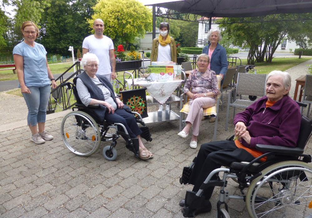 Von links: Ergotherapeutin Ina Halbe, Pflegekraft Leons und Maskennäherin Bianca Marschall im Kreise einiger Bewohner der Seniorenbetreuung Schloß Schliestedt vor den angeschafften Bingo- und Dartspielen sowie den Büchern auf dem Wagen.