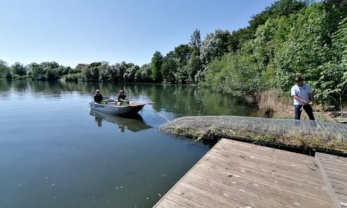 Mitarbeiter der WEB ziehen eine bepflanzte schwimmende Insel in den Neuen Teich.