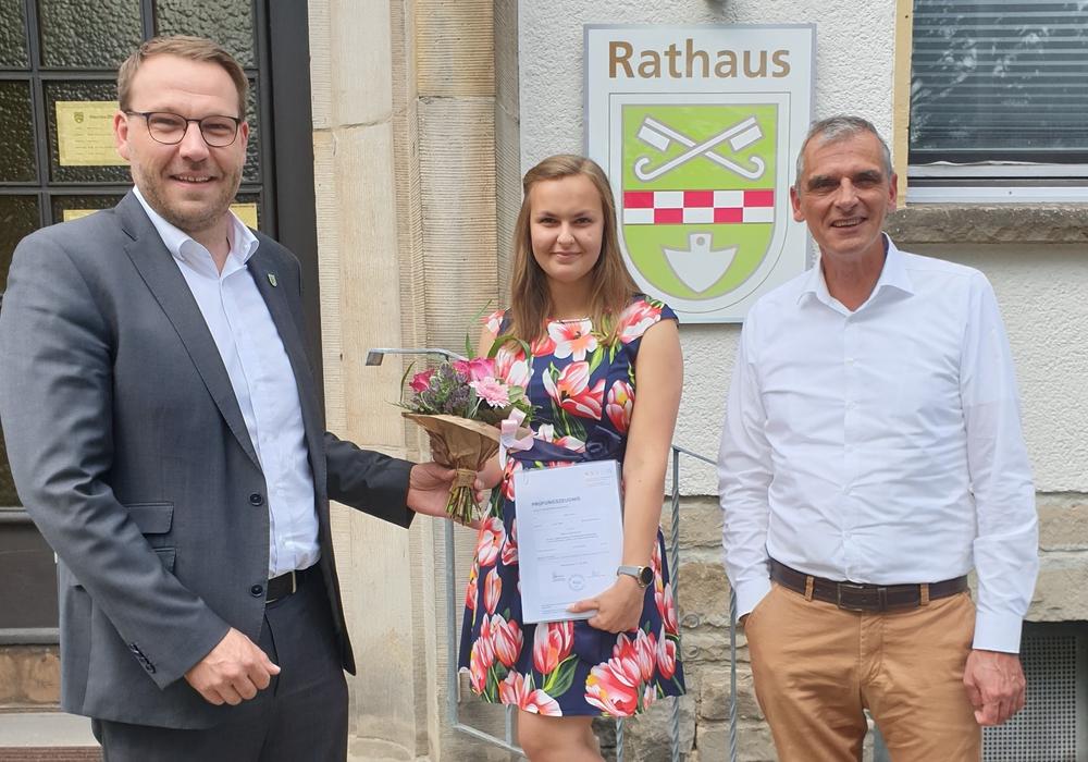 Samtgemeindebürgermeister Gero Janze (links) und Fachbereichsleiter Kai-Stephan Schulz (rechts) gratulieren Milita Jawni zur bestandenen Prüfung.