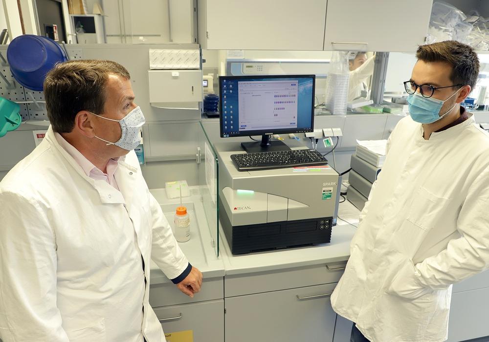 Promovend Alexander Heinz (r.) erklärt Axel Burghardt, Geschäftsführer des Klinikums Wolfenbüttel, wie die Tests auf Covid-19 im Labor des BRICS ausgewertet werden.