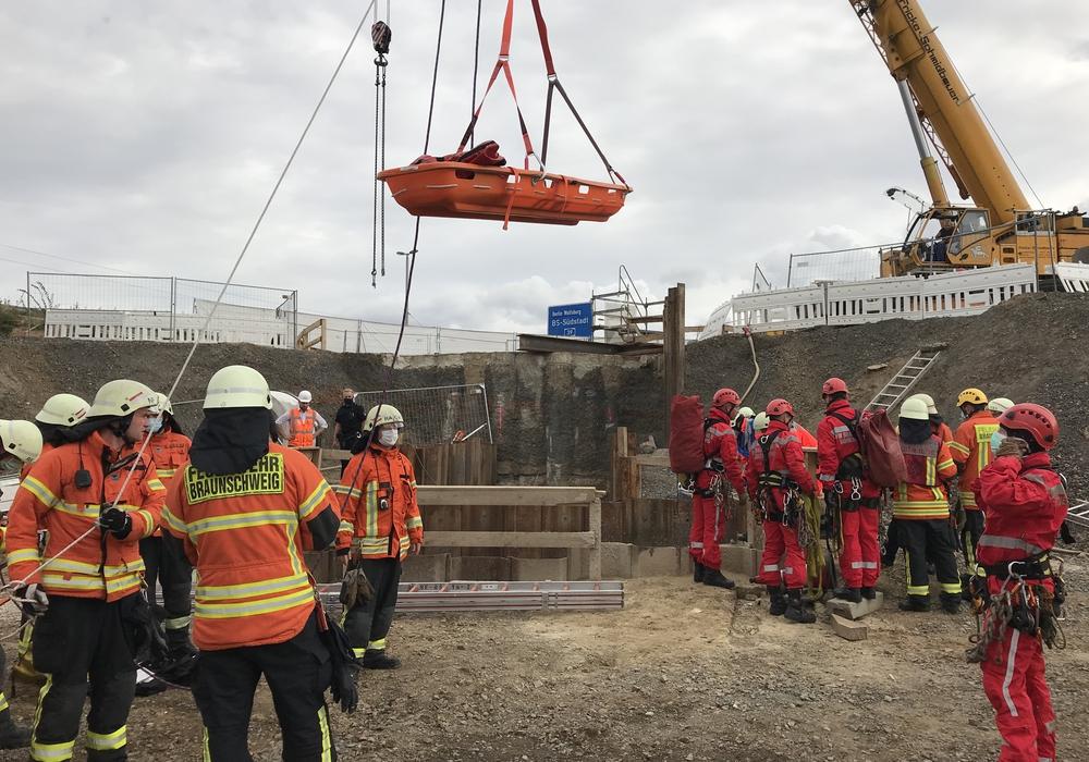 Die Feuerwehr bringt eine Rettungstrage, befestigt an einem Drehleiterfahrzeug in Position. Im Hintergrund die mehrere Meter tiefe Baugrube.