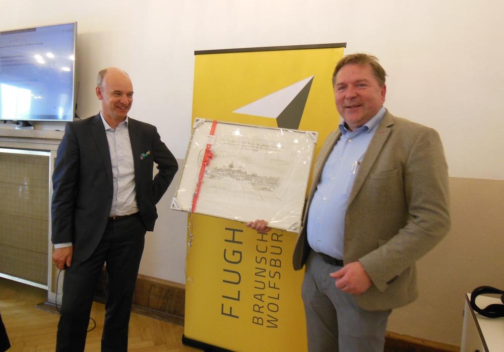 Aufsichtsratsvorsitzender Matthias Disterheft (rechts) überreicht dem ausgeschiedenen Aufsichtsratsmitglied der Flughafengesellschaft Christian Geiger eine historische Originalgrafik des Flughafengebäudes. Werner Borcherding konnte an der Sitzung nicht teilnehmen.