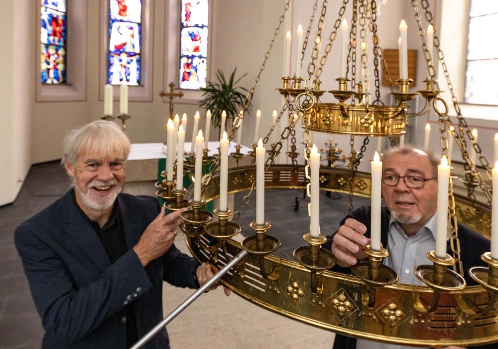 Pastor Uwe Teichmann und Elektromeister Herbert Lindhofer mit dem alten Kronleuchter in der Kirche.