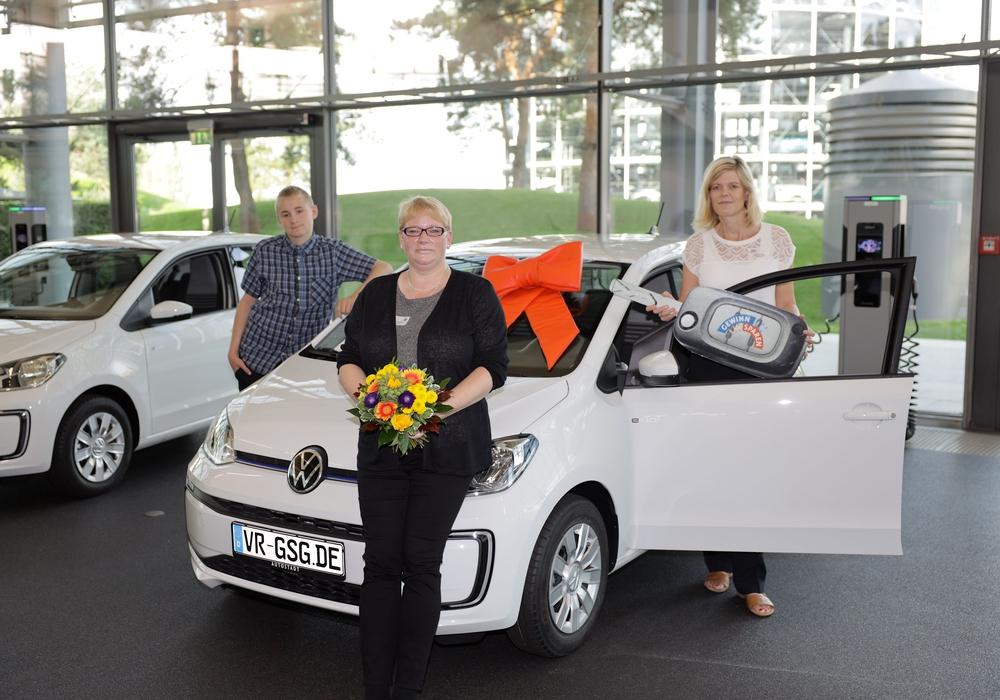 Amanda Busch und ihr Sohn Sohn Dustin Wiener können es noch nicht so richtig glauben. Sie nahmen einen neuen VW e-Up! von Nicole Pschak, Privatkundenberaterin bei der Volksbank BraWo (rechts), in der Autostadt Wolfsburg in Empfang.
