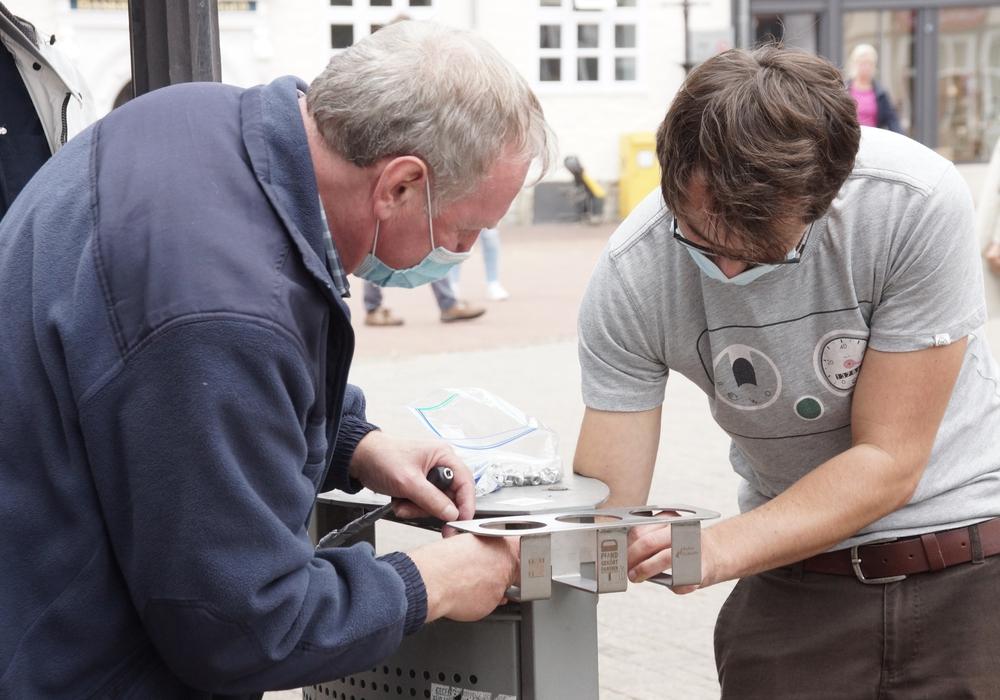 Rainer Demuth und Tim Hain bringen einen der neuen Pfandhalter an einem Mülleimer nahe des Rathauses an.