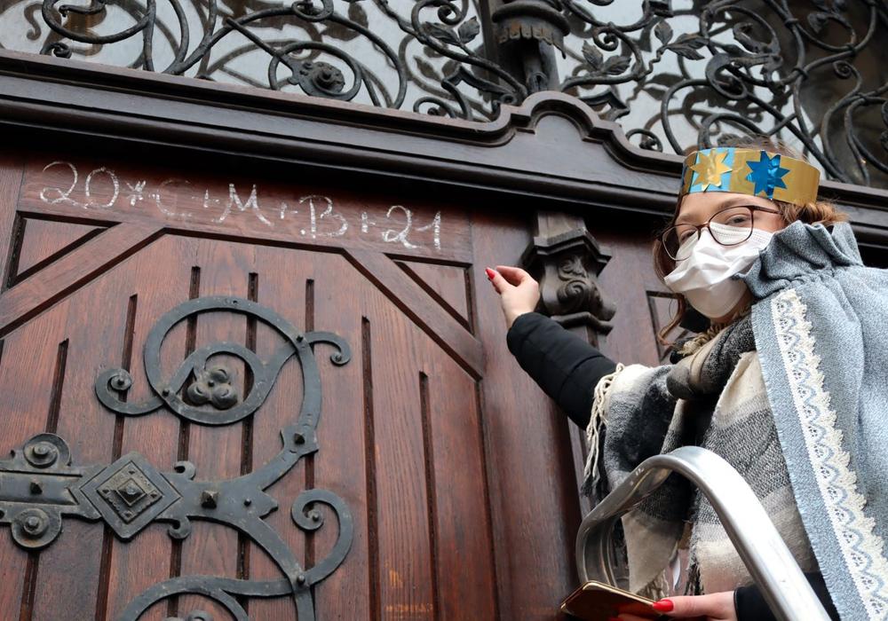 Sternsingerin Chantal schreibt den Segen an die Rathaustür.