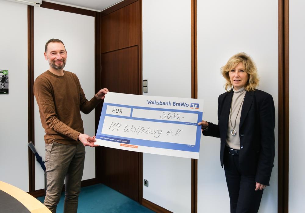 Stephan Ehlers, Geschäftsführer des VfL Wolfsburg e.V., nimmt den Spendenscheck von Claudia Kayser, Leiterin der Direktion Wolfsburg der Volksbank BraWo, entgegen.