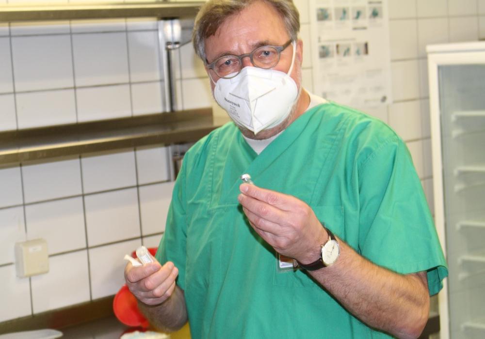 Der medizinische Leiter des Impfzentrums Prof. Dr. Karl Wessel erklärt, wie der Impfstoff angerührt werden muss.
