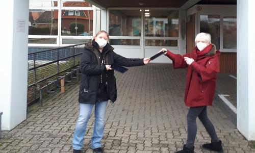 Yvonne Franke nimmt die Tabletts aus der Hand von Eva Fuhrmann entgegen.