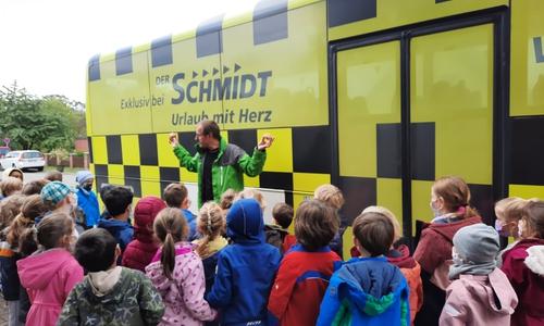 Hendrik Schmidt-Mühlen demonstriert den Erstklässlerinnen und Erstklässern die Kraft des rollenden Busses.