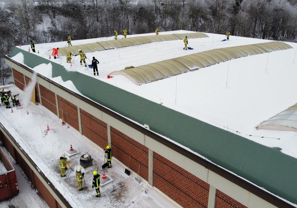 Feuerwehrleute befreien das Dach der Kanthalle von den Schneemassen.