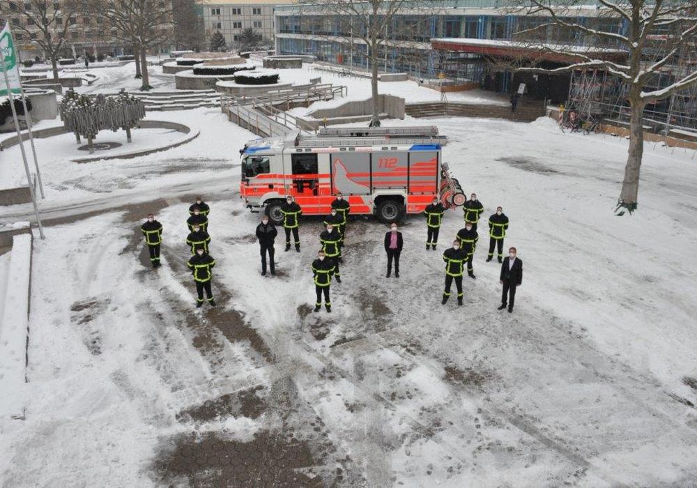 Mit Maske und Abstand stellten sich die neuen Kolleginnen und Kollegen der Berufsfeuerwehr gemeinsam auf dem Rathausvorplatz vor dem neuesten Löschfahrzeug der Berufsfeuerwehr auf.