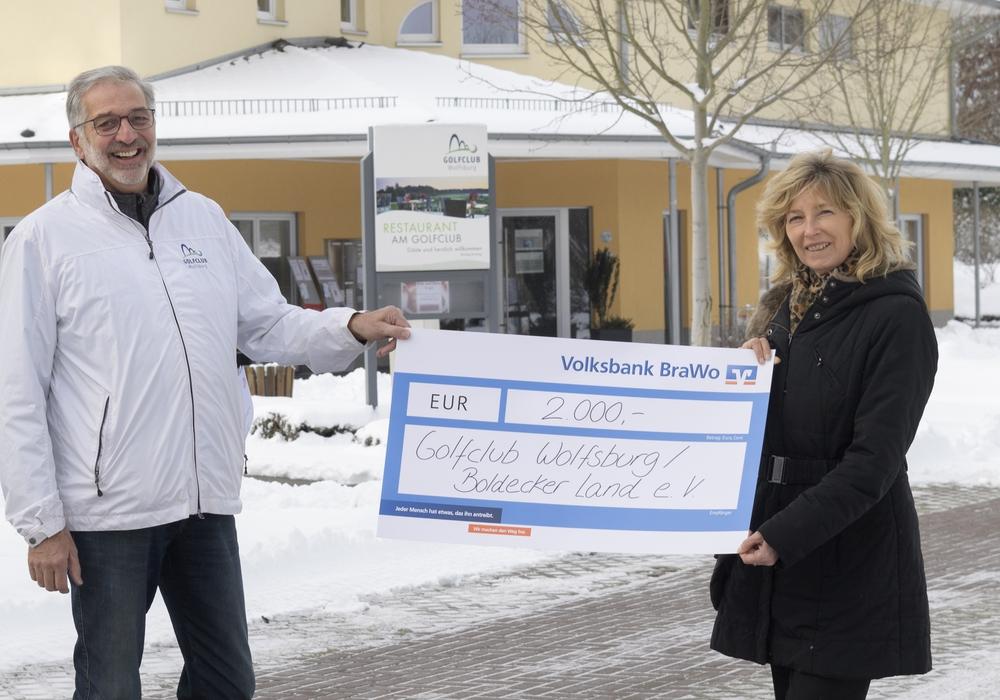 Norbert Preine, Präsident des Vorstandes des Golfclubs, nimmt die Spende symbolisch von Claudia Kayser, Leiterin der Direktion Wolfsburg der Volksbank BraWo, entgegen.