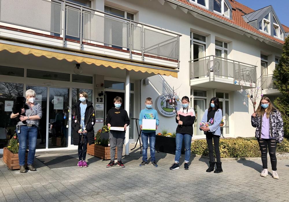 Schüler des 7. Jahrgangs der OBS Sickte übergeben die Osterbasteleien an Petra Loges ((links), Leiterin des Seniorenzentrums am Herrenhaus Sickte.