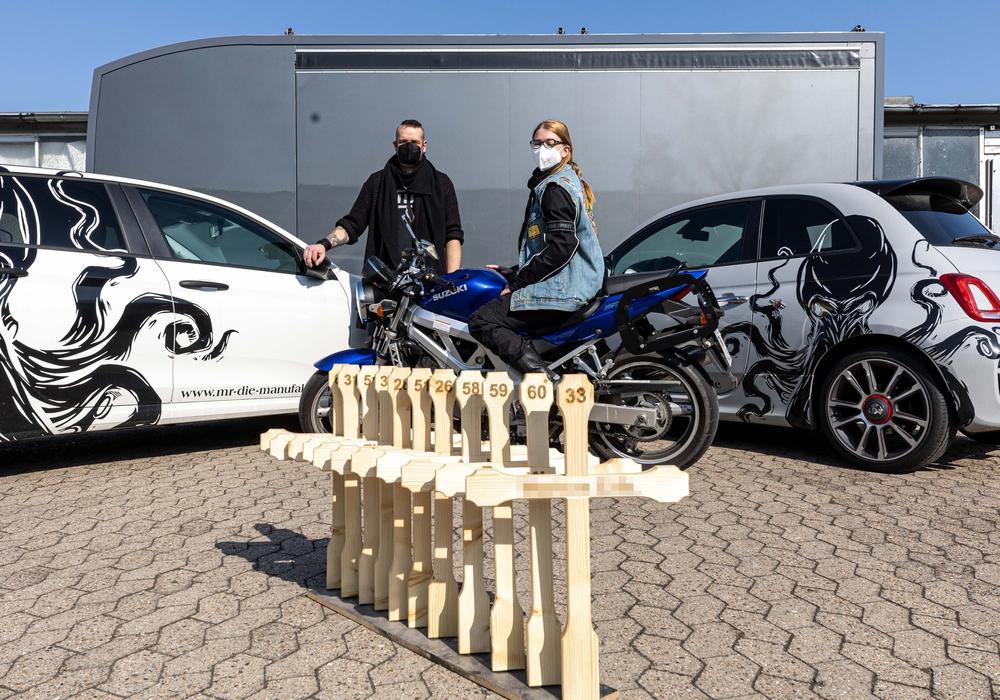 Die Elf Holzkreuze stehen für die Verstorbenen in der Motorradsaison 2020. Im Hintergrund: Marc Kiefer, Geschäftsführer des Messebauers MR - Die Manufaktur und Tina Wachter, stellvertretende Vorsitzende des ACM.
