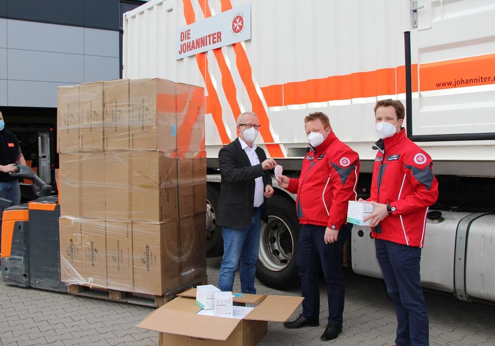 Michael Uphaus von der Perschmann Gruppe (2. von links) übergibt die Atemschutzmasken an Marc Wegner von den Johannitern (2. von rechts) und seinen Kollegen Michael Fricke. Links im Bild steht Robert Haller, Mitarbeiter im Wareneingang von Perschmann.