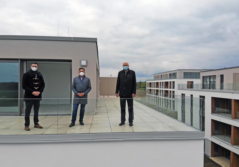 """Maximilian Bohr (Abteilungsleiter Individualkunden BS Energy), Thorsten Schmidt (Geschäftsführer Bauunternehmen Schmidt GmbH & Co.KG ) und Kai-Uwe Rothe (Geschäftsführer BS Netz) über den Dächern des Baugebietes """"Neue Mitte"""" in Lamme (v. li.)."""