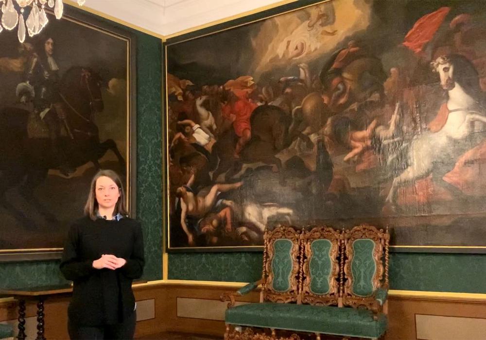 Wissenschaftliche Volontärin Stella Gilfert vor dem historischen Gemälde.
