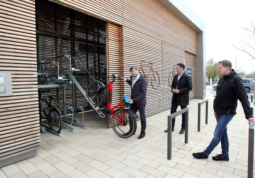 Fahrradbeauftragter Oliver Bley schiebt ein Rad in die Box, daneben BM Matthias Nerlich und Karsten Moritz, Fachbereichsleiter Bauverwaltung.