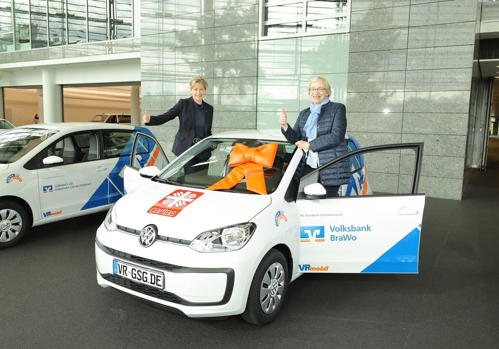 """Claudia Kayser (l.), Leiterin der Direktion Wolfsburg der Volksbank BraWo, übergibt das """"VRmobil"""", einen VW up!, an Barbara-Maria Cromberg, Vorständin des Caritasverband Wolfsburg e.V."""