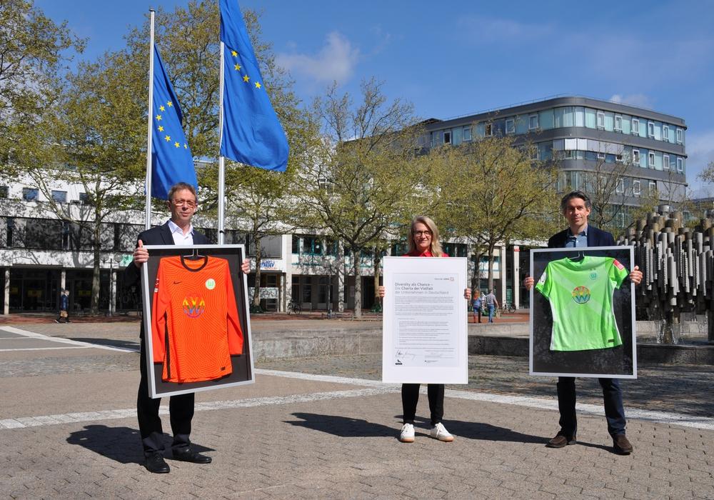 Michael Meeske (r.) übergibt die Regenbogentrikots an Oberbürgermeister Klaus Mohrs und Antje Biniek.