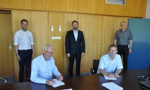 Oberbürgermeister Klaus Mohrs und Ernst-Dietrich Braetsch (Deutsche Glasfaser, vorne links) unterzeichneten den Kooperationsvertrag im Beisein von (hinten, von links) Dennis Weilmann, Christof Martin Milek (Deutsche Glasfaser) und Kai-Uwe Hirschheide.