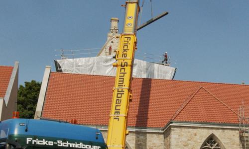 Der Kran hob die schweren Dachteile auf das Gebäude.