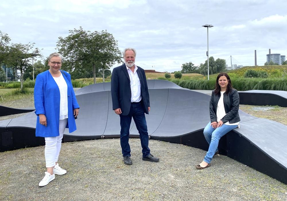 Iris Bothe, Götz Stehr (Leiter Geschäftsbereich Grün) und Katharina Varga (Leiterin Geschäftsbereich Jugend) an dem neuen Pump Track im Allerpark.
