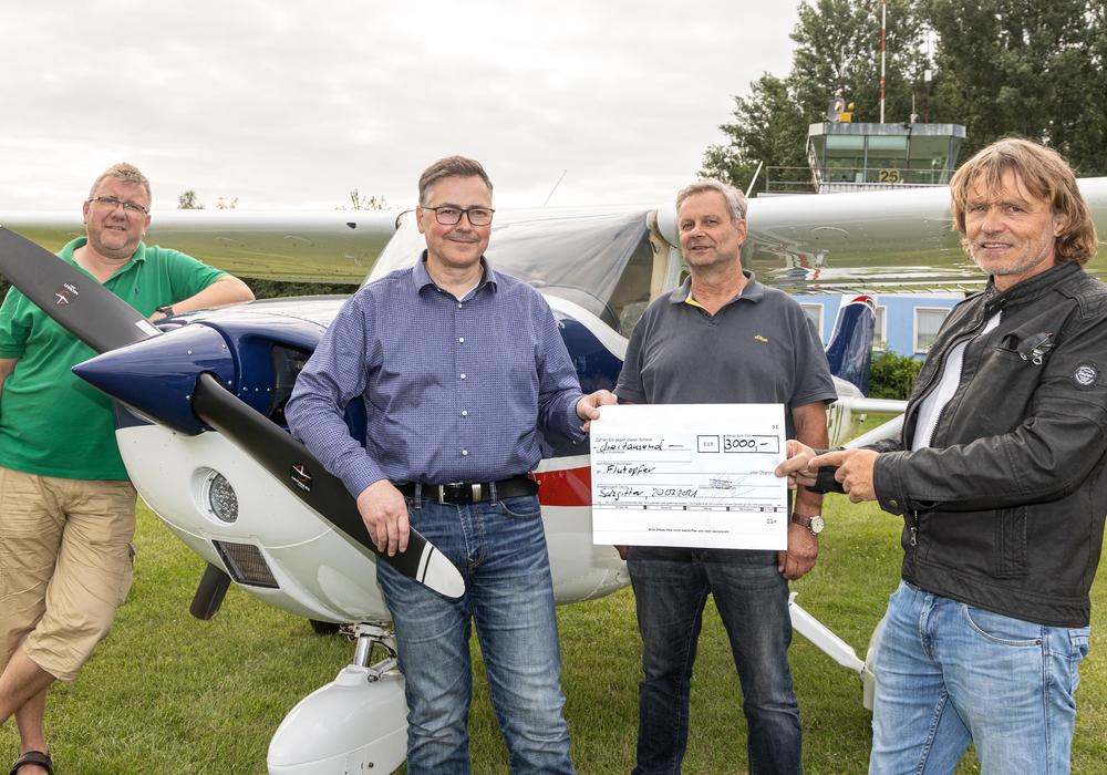 Sebastian Ratajczak, Stephen Buchholz (Flugleiter), Wolfram Ziegler (Flugzeugwart) und Jürgen Grubba (erster Vorsitzender) bei der Spendenübergabe.